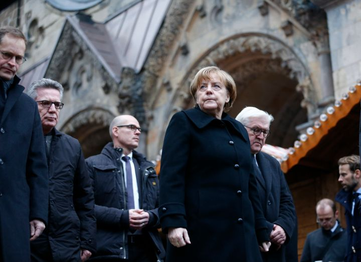 German Chancellor Angela Merkel and German Foreign Minister Frank-Walter Steinmeier walk towards the Christmas market in Berl