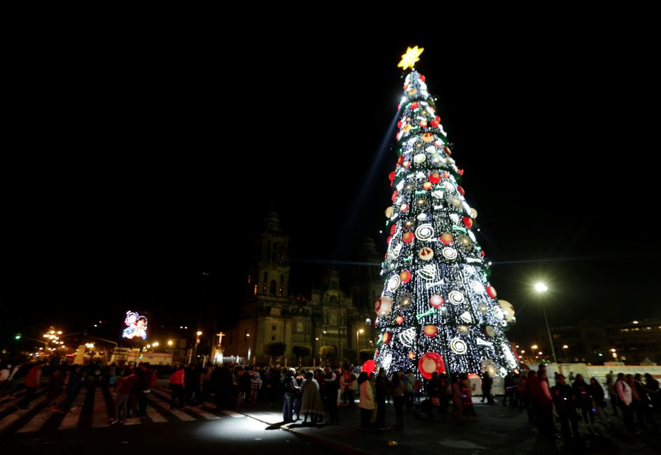 People are seen near a Christmas tree and buildings around the Zócalo as part of Christmas celebrations in Mexico City