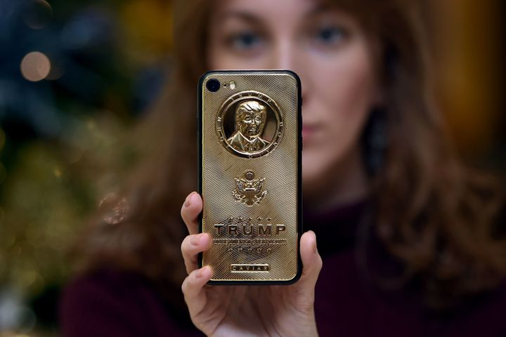 An employee of Caviar Phones shows off a more affordable version of a gold-plated Trump smartphone.