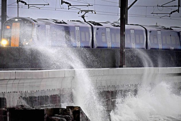 A Scotrail train passes waves crashing against the new weather defences at Saltcoats
