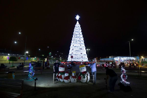 People pose in front of an illuminated Christmas tree in a park in Machala, Ecuador, on December 14, 2016.