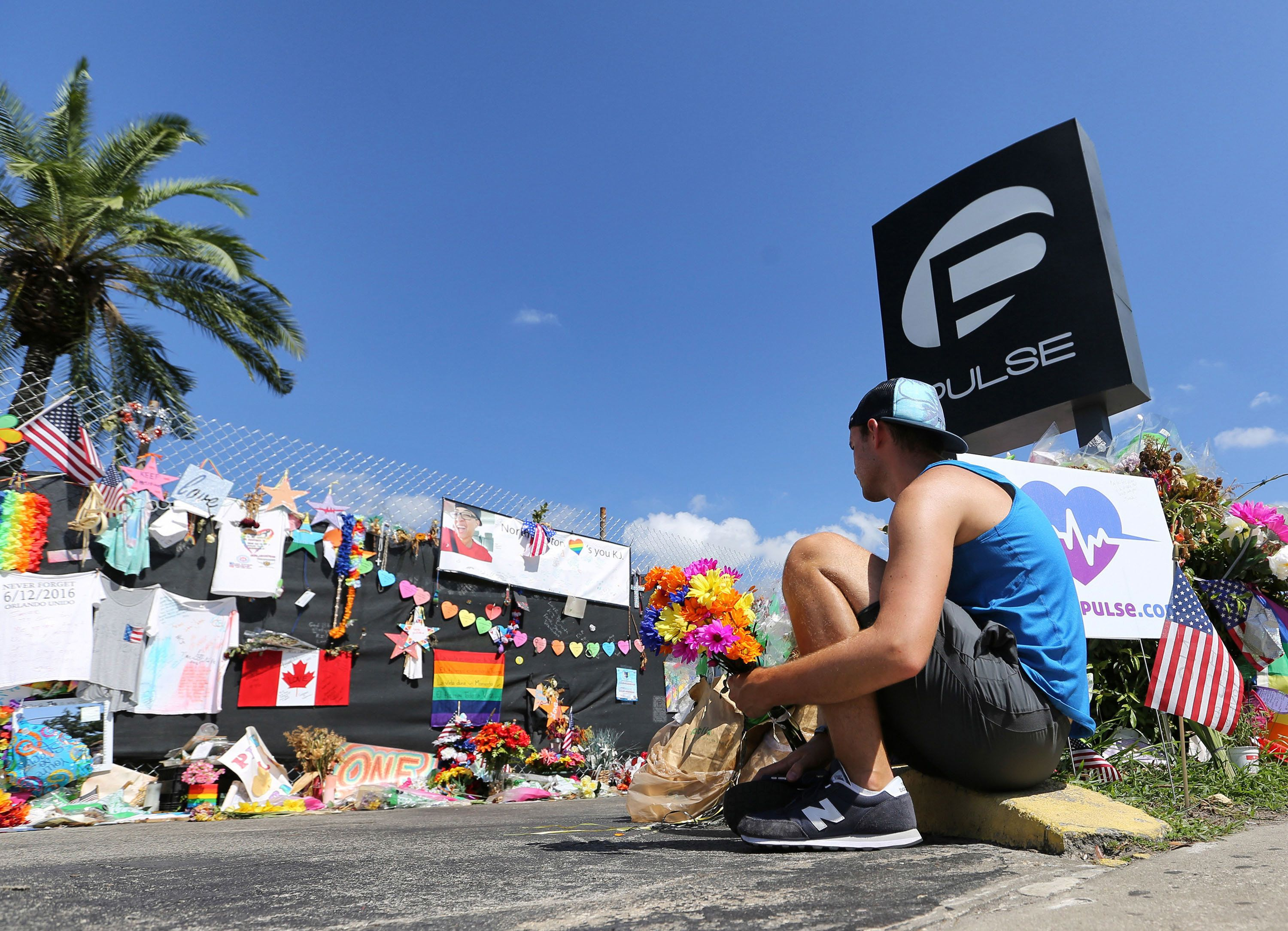 On the eve of the one-month anniversary of the Pulse nightclub massacre, a friend of two of the victims places flowers as visitors continue to flock to the club to their pay their respects on Monday, July 11, 2016 in Orlando, Fla. Today, family members of those who died will tell an Orlando judge what they want done with the recordings of 911 calls from that night.  (Joe Burbank/Orlando Sentinel/TNS via Getty Images)