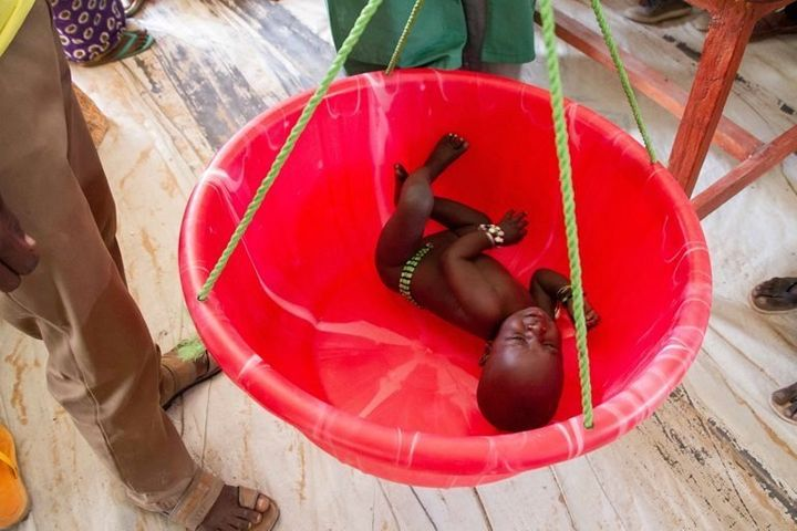 An infant is weighed at the Dar es Salaam refugee camp.