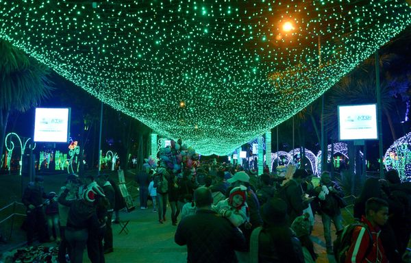 People walk along a park that has been illuminated for Christmas in Bogotá on December 17, 2015.