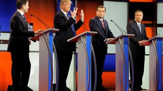 Republican U.S. presidential candidate Donald Trump shows off the size of his hands as rivals Marco Rubio (L), Ted Cruz (2nd R) and John Kasich (R) look on at the start of the U.S. Republican presidential candidates debate in Detroit, Michigan, U.S., March 3, 2016. REUTERS/Jim Young/File Photo