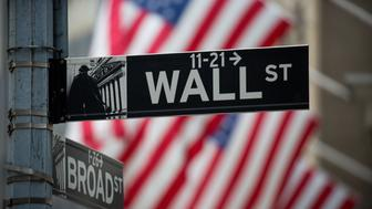 A Wall Street sign is displayed as American flags fly in front of the New York Stock Exchange (NYSE) in New York, U.S., on Monday, Nov. 21, 2016. U.S. stocks were set for the highest closing level on record, led by energy companies, as oil jumped on optimism OPEC will agree to cut output. Photographer: Michael Nagle/Bloomberg via Getty Images