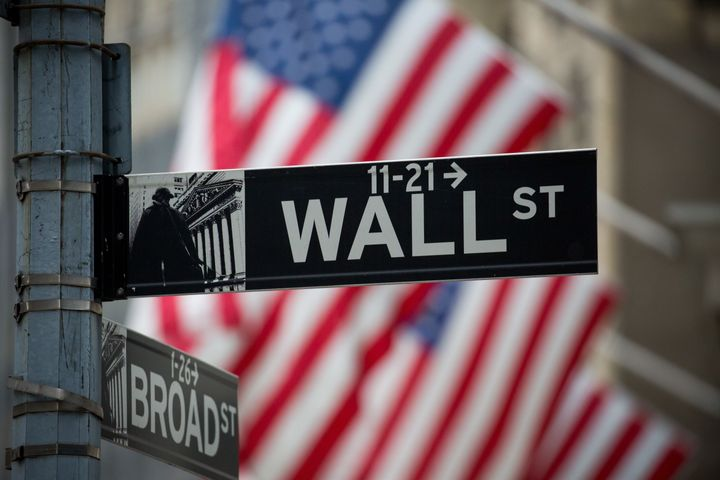 A Wall Street sign is displayed as American flags fly in front of the New York Stock Exchange (NYSE) in New York, U.S., on Mo