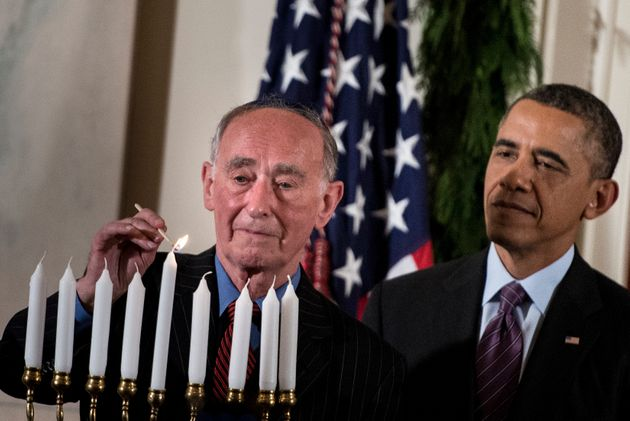 President Barack Obama watches as Martin Weiss, a Holocaust survivor, lights a menorah during a Hanukkah...