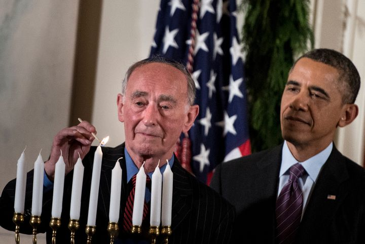 President Barack Obama watches as Martin Weiss, a Holocaust survivor, lights a menorah during a Hanukkah reception in the Whi