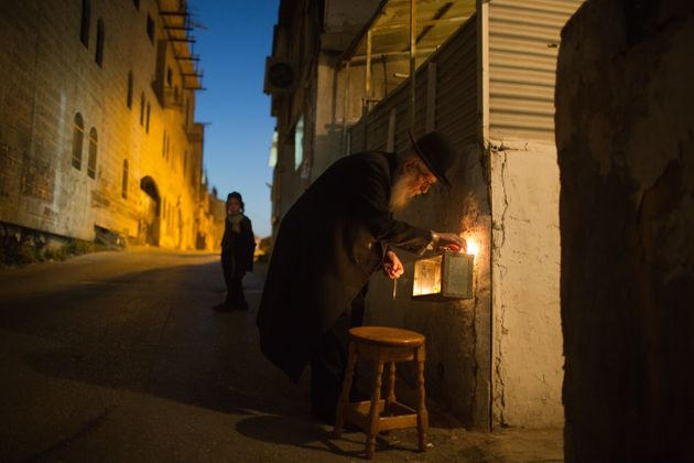 An ultra-orthodox Jewish man lights candles on the sixth night of the Jewish holiday of Hanukkah, in...
