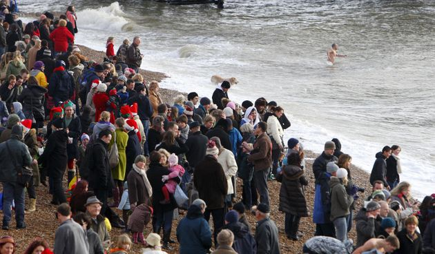 Spectators gather on the beach to watch the few dozen foolhardy swimmers on Christmas