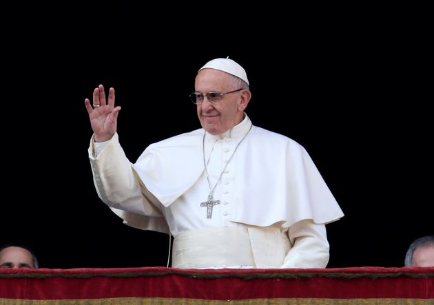Pope Francis waves as he arrives to deliver the