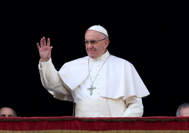 "Pope Francis waves as he arrives to deliver the ""Urbi et Orbi"" message from the balcony overlooking St. Peter's Square at the"