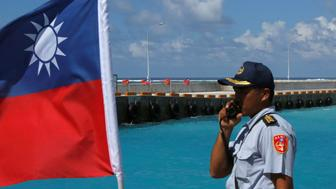 A member of the Taiwanese Coast Guard stands guard next to a Taiwanese flag on Itu Aba, which the Taiwanese call Taiping, at the South China Sea, November 29, 2016. REUTERS/J.R Wu