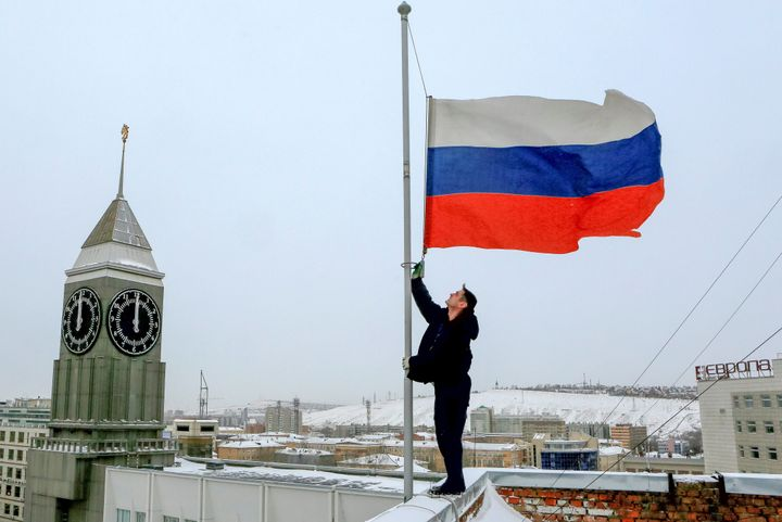A worker lowers the Russian national flag to half-mast on a roof of Krasnoyarsk's administration building, as the country obs