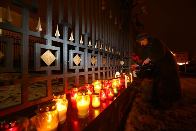 A woman lays flowers at the Russian embassy in Minsk, Belarus, in memory of passengers and crew members...