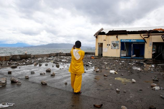 A port worker stands amidst debris swept from the sea at the height of Typhoon Nock Ten in Mabini, Batangas,...
