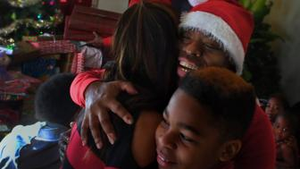 OXEN HILL, MD-DEC 25: Tyshika Britten gives a hug of thanks (with her son Na'zhia Bolden, 11) to Shirley Luu, a local business woman who stopped by to give the family some gifts and money. This is a Christmas Day follow-up to the viral story about Tyshika Britten who went on craigslist saying she was a failure and asked for help on Christmas because the family was out of money. Donations and presents came in from around the country, including Eddie Vedder. (Photo by Michael S. Williamson/The Washington Post via Getty Images)