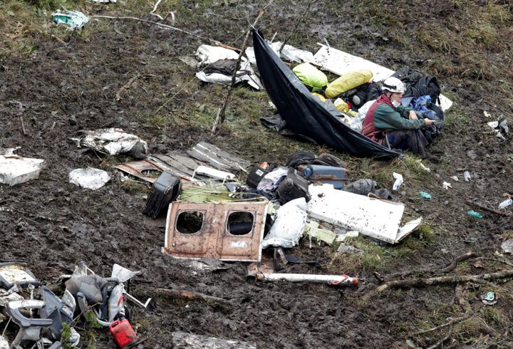 A rescue worker sits near the wreckage of a plane that crashed into the Colombian jungle with Brazilian soccer team Chapecoen