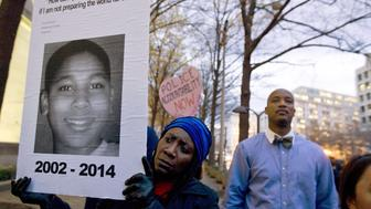 FILE - In a Monday, Dec. 1, 2014 file photo, Tomiko Shine holds up a picture of Tamir Rice during a protest in Washington, D.C. The gazebo where the 12-year-old boy, Rice, was fatally shot by a Cleveland police officer is scheduled to be disassembled. A spokesman for the Stony Island Arts Bank says the shingles will be removed on Wednesday, Sept. 14, 2016, with work continuing into next week. (AP Photo/Jose Luis Magana, File)