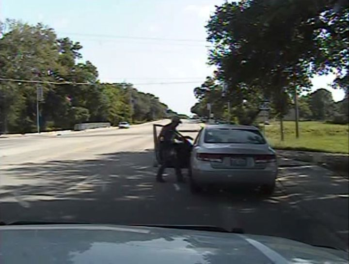 Texas state trooper Brian Encinia points a Taser, in this still image captured from the police dash camera video from the tra