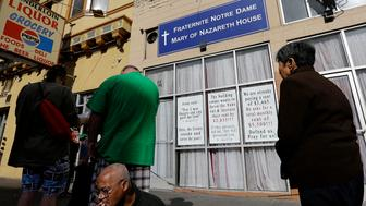 Signs hang on the front of the Fraternite Notre Dame Mary of Nazareth Soup Kitchen behind a line of people waiting for food to be served in San Francisco, Tuesday, Feb. 9, 2016. SanFrancisco nuns who serve the homeless are in danger of getting kicked out of their home after a rent hike of more than 50 percent. (AP Photo/Jeff Chiu)