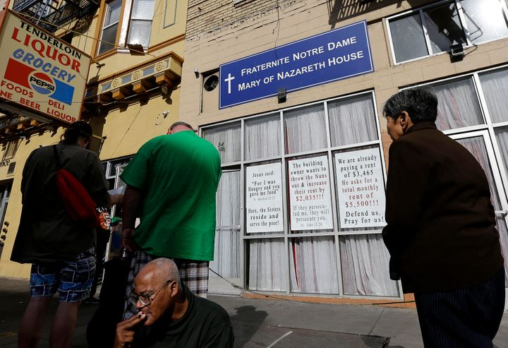 Signs hang on the front of the Fraternite Notre Dame Mary of Nazareth Soup Kitchen behind a line of people waiting for food t
