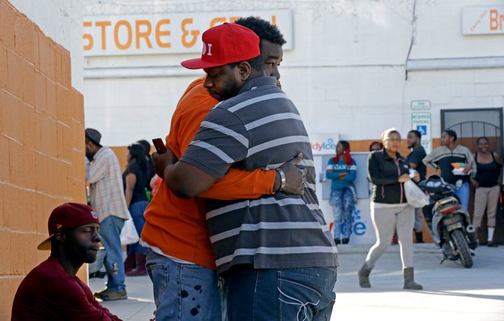 Two men embrace near the scene of a fatal shooting in Raleigh, N.C., Monday, Feb. 29, 2016. Authorities say that a police off