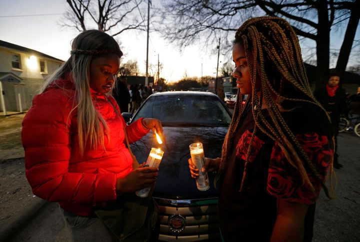 Destiny Brown, left, and Bonnie King light candles during a vigil near the scene of a fatal shooting in Raleigh, N.C., Monday
