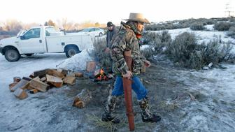 FILE - In this Jan. 6, 2016 file photo, Arizona rancher Robert LaVoy Finicum carries a rifle after standing guard all night at the Malheur National Wildlife Refuge near Burns, Ore. On Tuesday, March 8, 2016, authorities said police were justified in killing Finicum during a traffic stop on Jan. 26, 2016. (AP photo/Rick Bowmer, file)