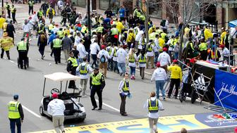 First responders rush to where two explosions occurred along the final stretch of the Boston Marathon on Boylston Street in Boston, Massachusetts, U.S., on Monday, April 15, 2013. Two powerful explosions rocked the finish line area of the Boston Marathon near Copley Square and police said many people were injured. Photographer: Kelvin Ma/Bloomberg via Getty Images
