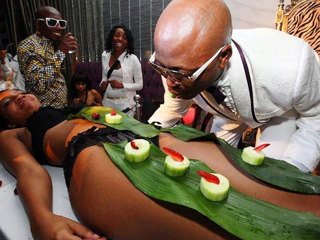 South African tycoon and socialite Kenny Kunene eating sushi from a model's naked body during one of his lavish birthday part