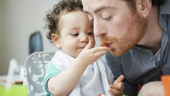 young child feeding father
