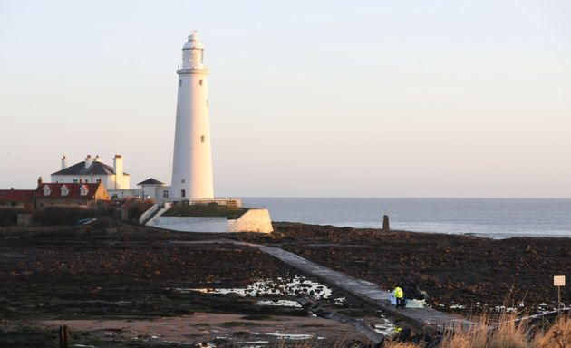 A car on its roof lies on the causeway at St Mary's Lighthouse, Whitley