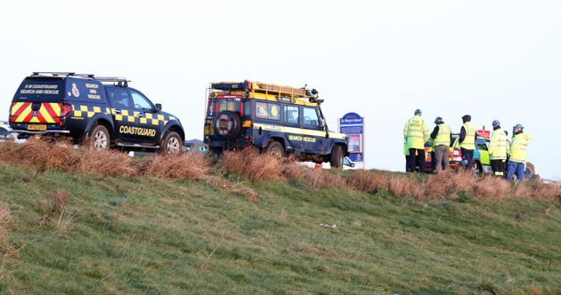 Coastguard in attendance as a car on its roof lies on the causeway at St Mary's Lighthouse, Whitley
