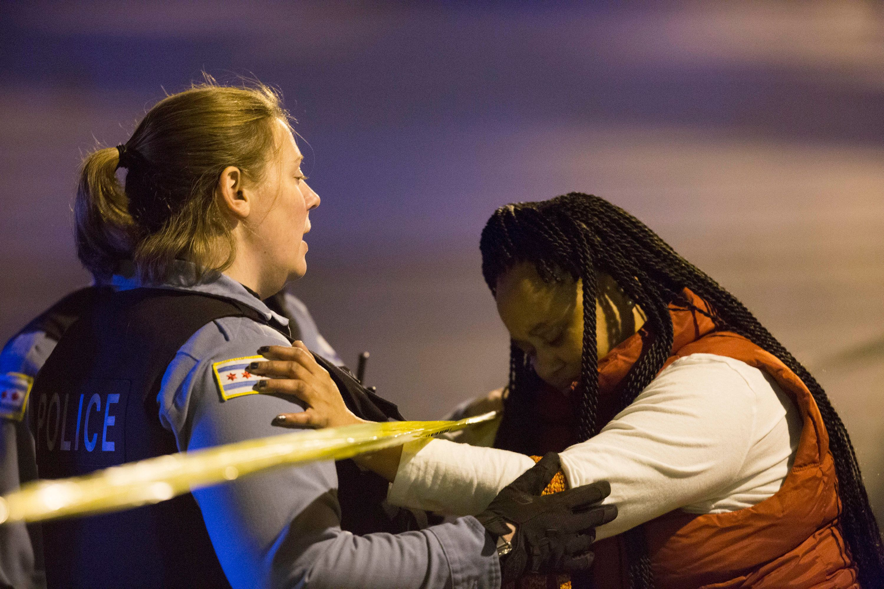A member of the Chicago Police Department talks with Felicia Humphries at the scene where her son was shot and killed near th