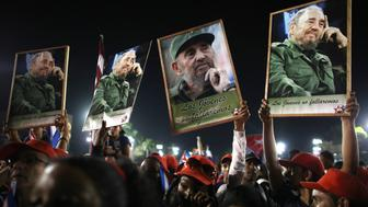 People hold up images of former Cuban leader Fidel Castro at a tribute to Castro in Santiago de Cuba, Cuba, December 3, 2016.            REUTERS/Alexandre Meneghini