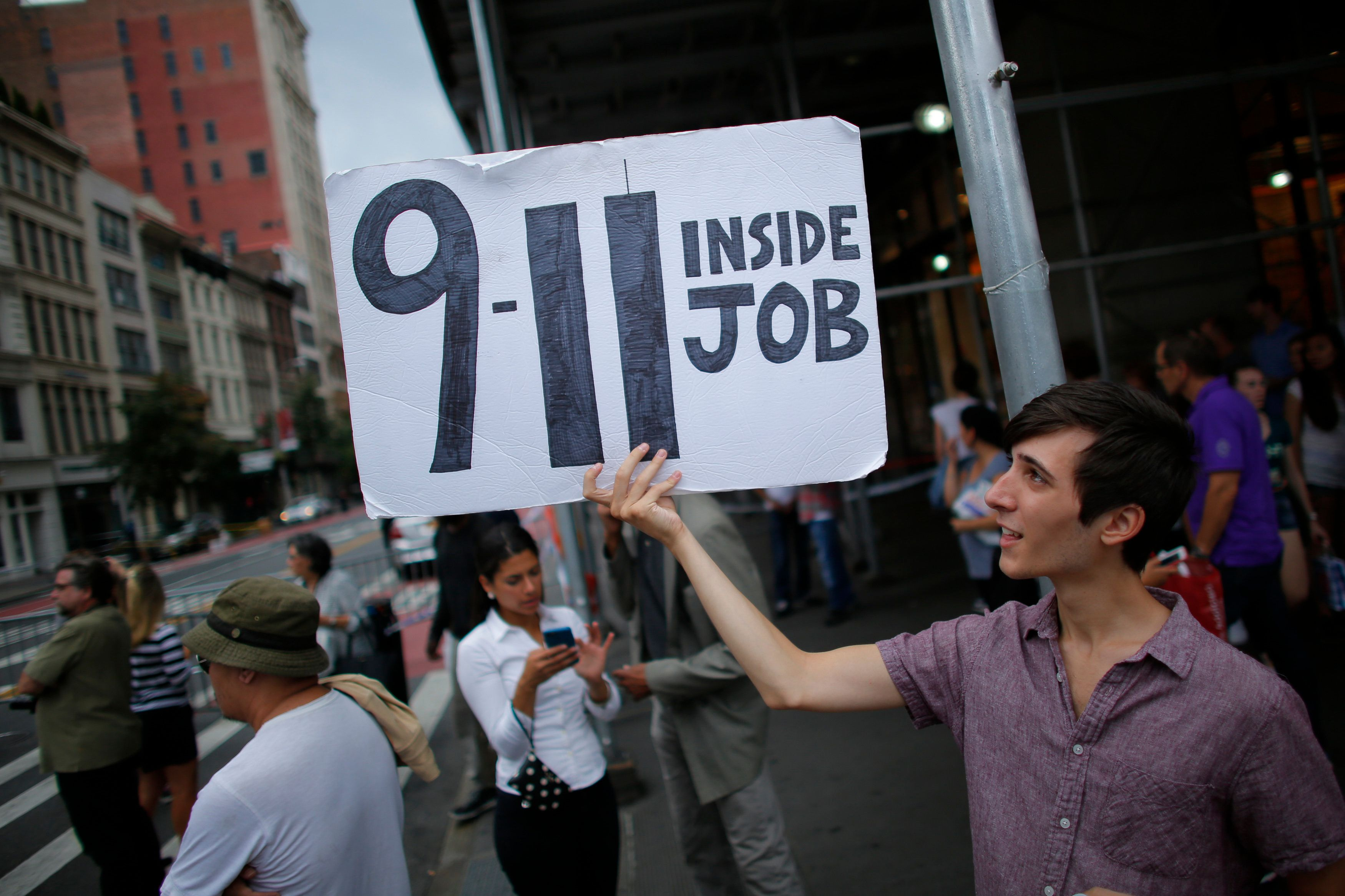 A man holds up a placard as sign of protest near to the scene of an explosion on West 23rd Street September,...