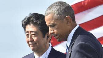 US President Barack Obama (R) walks with Japanese Prime Minister Shinzo Abe  after they spoke on Kilo pier near the USS Arizona Memorial December 27, 2016 at Pearl Harbor in Honolulu, Hawaii.  Abe and Obama made a joint pilgrimage to the site of the Pearl Harbor attack on Tuesday to celebrate 'the power of reconciliation. 'The Japanese attack on an unsuspecting US fleet moored at Pearl Harbor turned the Pacific into a cauldron of conflict -- more than 2,400 were killed and a reluctant America was drawn into World War II. / AFP / Nicholas Kamm        (Photo credit should read NICHOLAS KAMM/AFP/Getty Images)