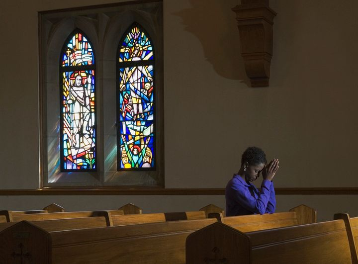 A woman prays inside a church.
