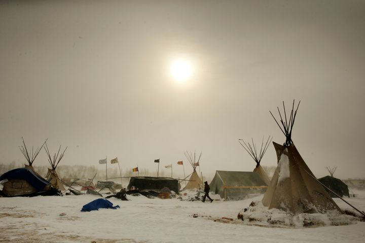 "A camper walks through high winds during a blizzard inside the Oceti Sakowin camp as ""water protectors"" continue to demonstra"