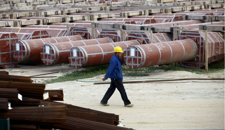 A Chinese worker walks at the construction site of the new Great Mosque, which is being built by the China State Construction