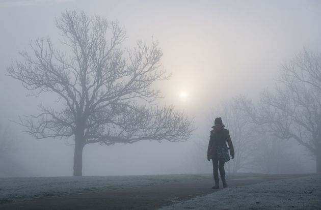 A woman walks in the fog at Blythe Hill Fields, in south east