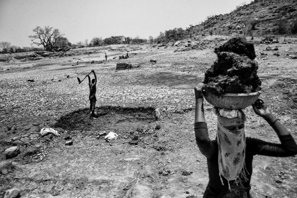 In the sweltering heat in Bundelkhand, a man and his wife remove silt from the bottom of a dried-out pond.