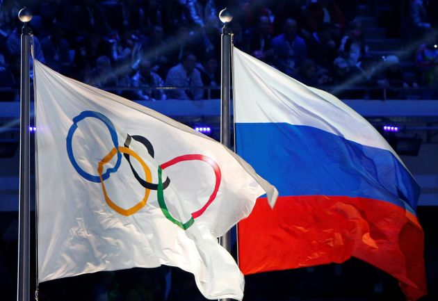 The Russian national flag (R) and the Olympic flag are seen during the closing ceremony for the 2014...