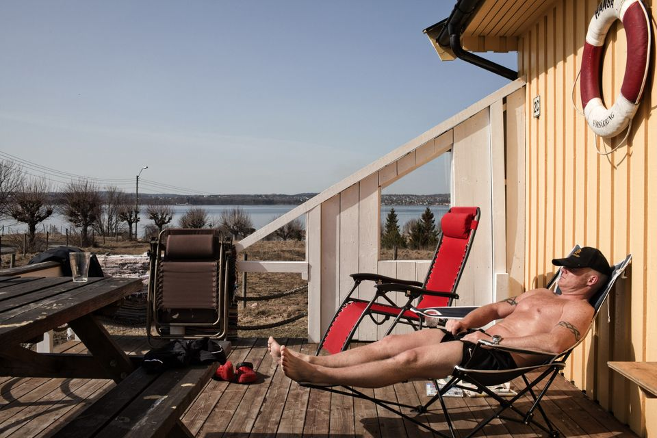 An inmate sunbathing in front of a wooden cottage in Bastoy Prison in Norway in April