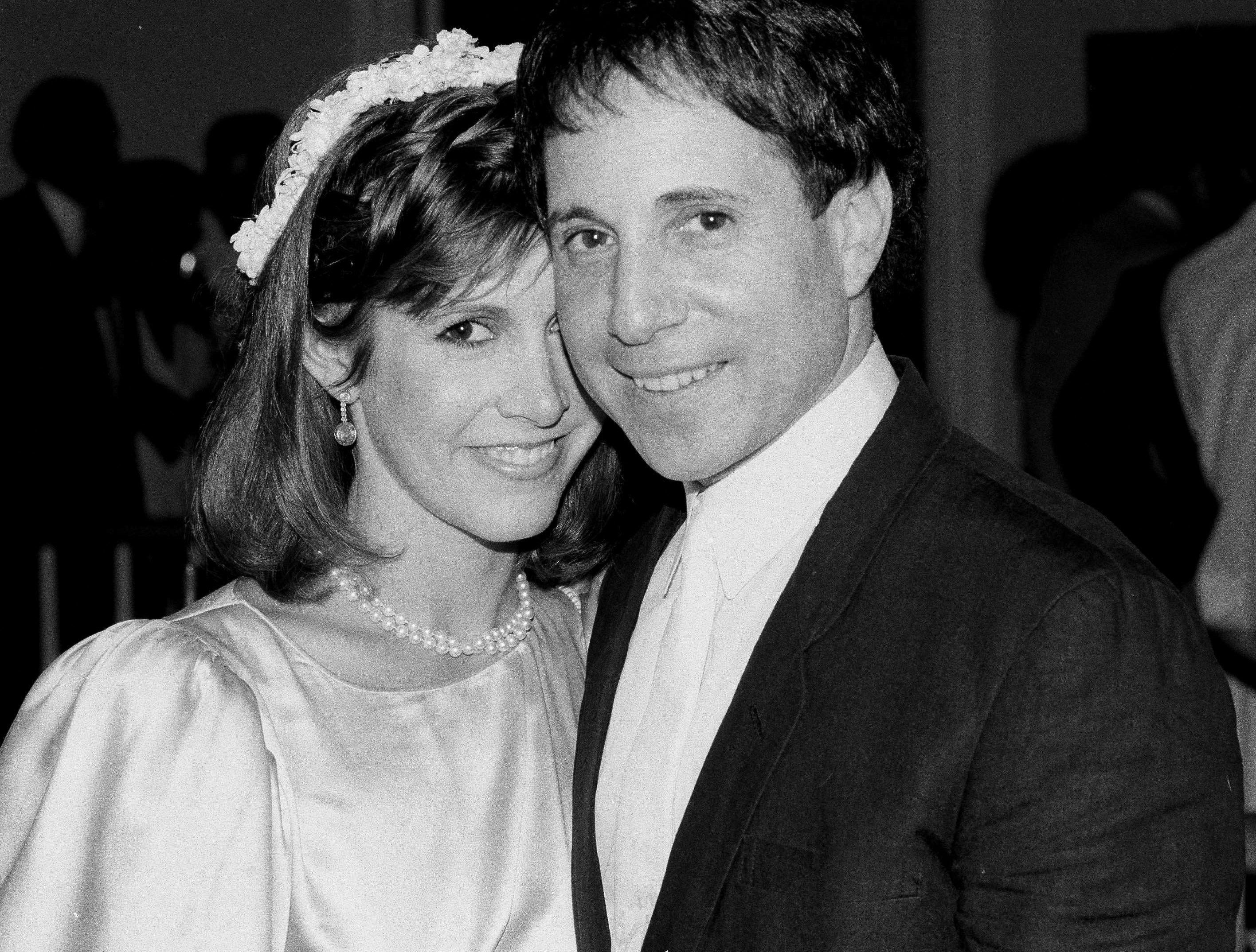 FILE - In this March 11, 1982 file photo, actress Carrie Fisher and singer-composer Paul Simon leave the Cathedral of St. John the Divine in New York, after a memorial service for comedian John Belushi. On Tuesday, Dec. 27, 2016, a publicist says Fisher has died at the age of 60. (AP Photo/Marty Lederhandler, File)