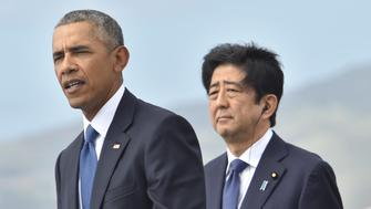 US President Barack Obama (L) speaks as Japanese Prime Minister Shinzo Abe listens at the USS Arizona Memorial on December 27, 2016 at Pearl Harbor in Honolulu, Hawaii. Abe and Obama made a joint pilgrimage to the site of the Pearl Harbor attack on Tuesday to celebrate 'the power of reconciliation. 'The Japanese attack on an unsuspecting US fleet moored at Pearl Harbor turned the Pacific into a cauldron of conflict -- more than 2,400 were killed and a reluctant America was drawn into World War II. / AFP / Nicholas Kamm        (Photo credit should read NICHOLAS KAMM/AFP/Getty Images)