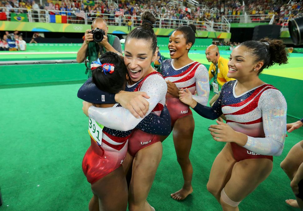 Simone Biles (USA) of USA (L) is hugged by team mates Alexandra Raisman (USA) of USA (Aly Raisman), Gabrielle Douglas (USA) o