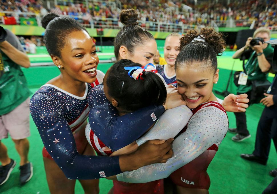 Simone Biles (USA) of USA (back-facing camera) is hugged by team mates (from L) Gabrielle Douglas (USA) of USA (Gabby Douglas